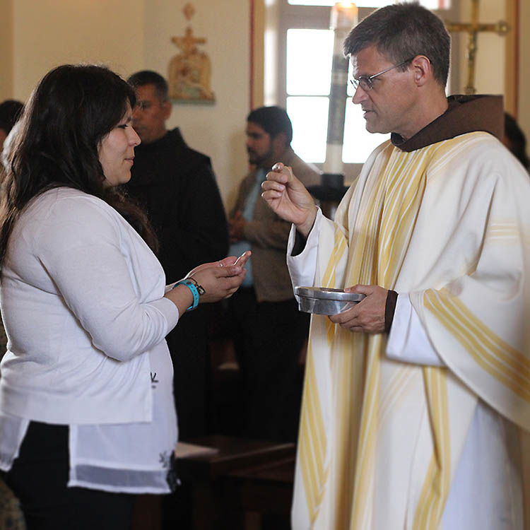 priest-giving-communion-to-staff